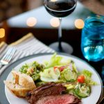 beautiful plate of tri tip with salad, and a glass of wine