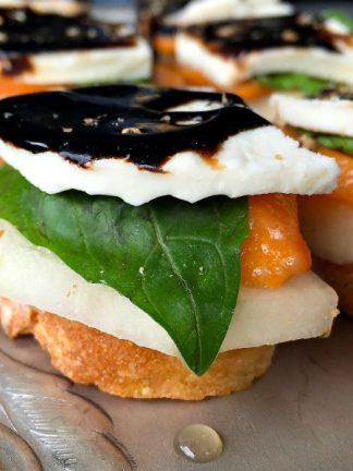 Persimmon Pear Caprese Crostini Appetizer: With creamy, fresh mozzarella, firm, sweet pears, and slices of persimmons, add a fresh basil leaf and serve on toasted crostini, drizzled with DeLallo's balsamic glaze!