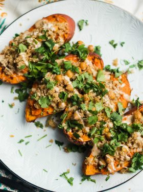 Tahini Stuffed Sweet Potatoes are a great weeknight meal, served with quinoa, garbanzo beans, tahini, and delicious spices. With a fork, mash the center of each sweet potato, filling with quinoa and chickpeas! Make a creamy tahini dressing and drizzle on top!