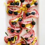 a white platter of salami pepperoncini rollups