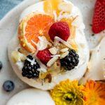 a mini pavlova with lemon curd, orange slice, berries, and coconut