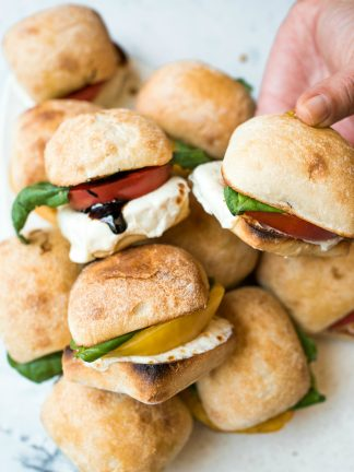 a platter of caprese sliders with heirloom tomatoes
