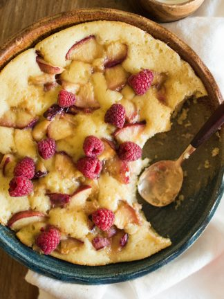 a round peach butter cake with raspberries on top