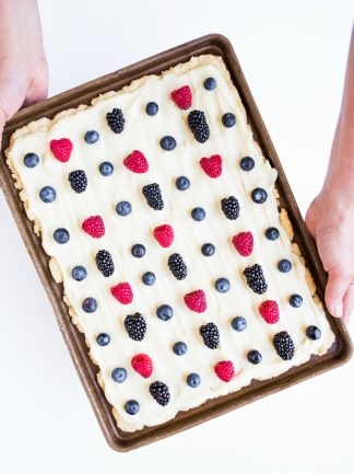 holding a baking sheet of sugar cookie bars with frosting and berries
