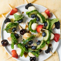 round plate of Summer Cucumber Bites on a Stick drizzled with balsamic glaze