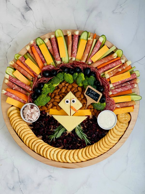 a round charcuterie plate shaped into a large turkey with veggies, meat, cheese, and crackers